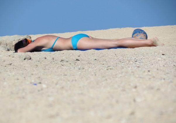 A woman lying face down in a blue bikini on the beach sunning. (Photo: Goodgood/Pixabay)