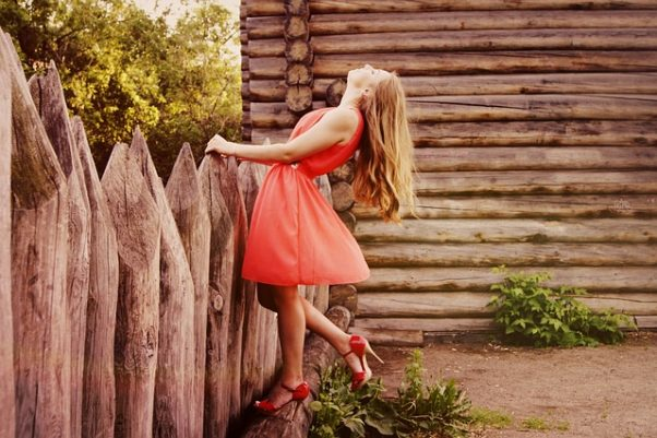 Woman in a red dress and heels sanding beside a rough wood fence and log cabin. (Photo: LisaLiza/Pixabay)