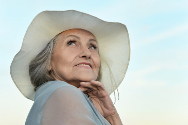 A gray haired woman in the sun wearing a wide-brimed hat. (Photo: Shutterstock)