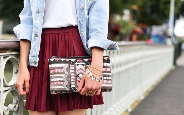 A woman in a red plaid skirt holding a clutch handbag and wearing a bracelet. (Photo: StockSnap/Pixabay)