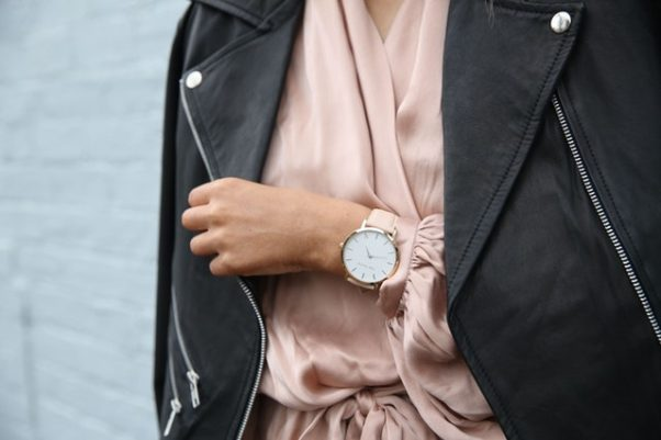 Closeup of a woman wearing a dress with leather jacket drapped over her shoulders and a watch. (Photo: The 5th/Pexels)