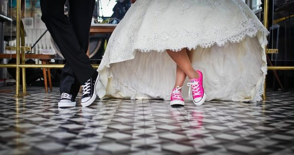 Groom wearing tux and black Chucks while bride in gown wears pink Chucks. (Photo: NGDPhotoworks/Pixabay)