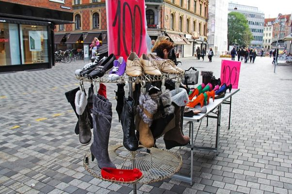 Assortment shoes on sale sitting on a table in an outdoor plaza. (Photo: sharonang/Pixabay)
