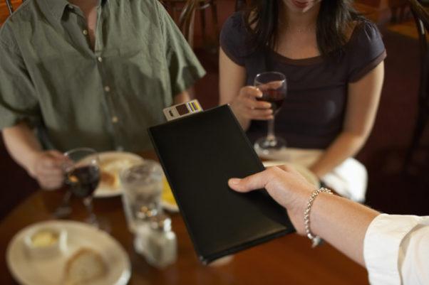 Waitress handing bill to couple in restaurant (Photo: Facebook)