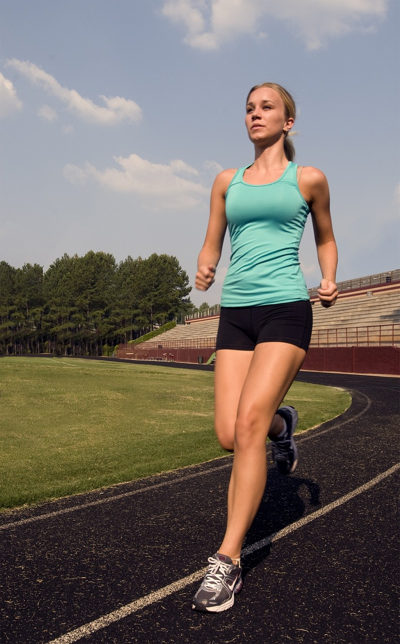 A woman in shorts and a tank top jogging on a track. (Photo: skeeze/Pixabay)