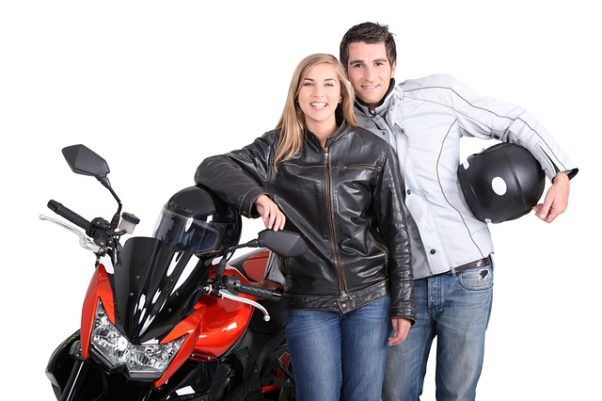 A woman and man leaning against a motorcycle holding helmets and wearing leather jackets. (Photo: peterlesliemorris/Pixabay)
