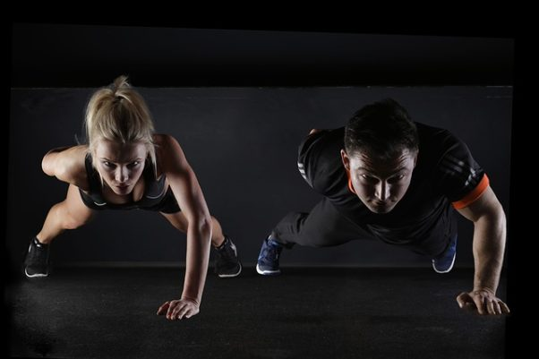 A man and woman side-by-side doing one handed pushups. (Photo: 5132824/Pixabay)
