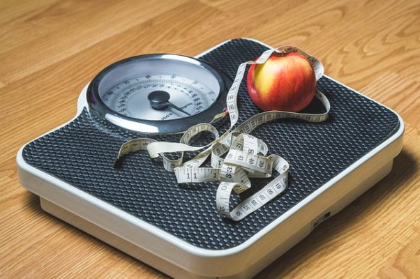 photo of a scale with an apple and tape measure on it. (Photo: TeroVesalainen/Pixabay)