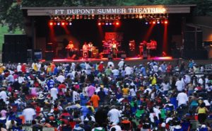 Crowds sitting on the lawn watch a band perform on stage at Fort Dupont Park. (Photo: National Park Service)