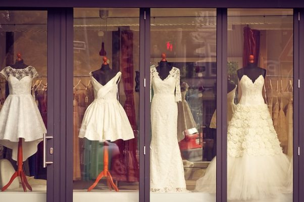 Four white wedding gowns of different lengths in a store window. A tailor's manequin, tape measure and old fashioned sewing machine. (Photo: nebulosagrafica/Pixabay)