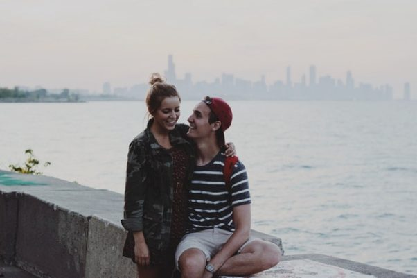 A couple sitting on a wall beside water with a city skyline in the background. (Photo: Snapwire/Pexels)