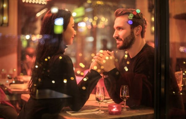 A couple sitting inside a restaurant holding hands. (Photo: Bruce Marks/Pexels)