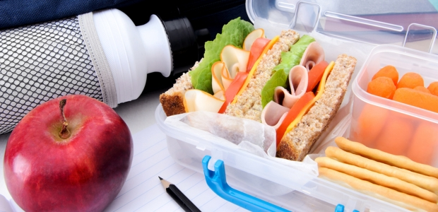 A lunchbox with a sandwich, fresh carrots, crackers, an apple and a bottle of water. (Photo: Shuttertsotck)