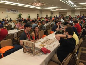 WashingCon attendees play a game in a ballroom filled with long tables and other game players. (Photo: WashinCon)
