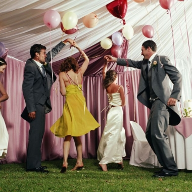 Two couples dancing at a wedding, with a single woman off to the left dancing by herself. (Photo: Getty Images)