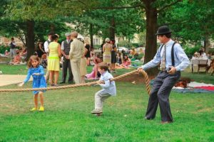 A man and two children playing tug-of-war while other talk and picnic in the background in period garb. (Photo: Nishell Falcone)