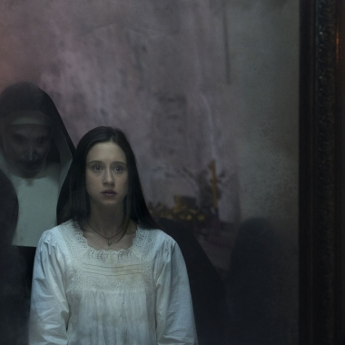 The evil nun looking over the shoulder of another nun in a mirror in The Nun. (Photo: Warner Bros. Pictures)