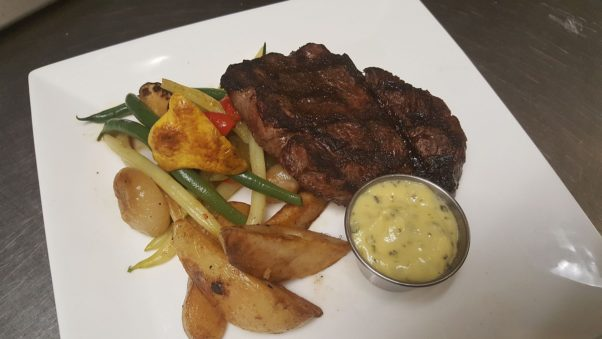 a ribeye steak on a plate with roasted fingerling potatoes and vegetables. (Photo: Bastille)