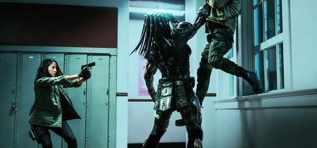 The Predator holding a man up in the air by his throat while Olivia Munn points a gun at the alien. (Photo: 20th Century Fox)