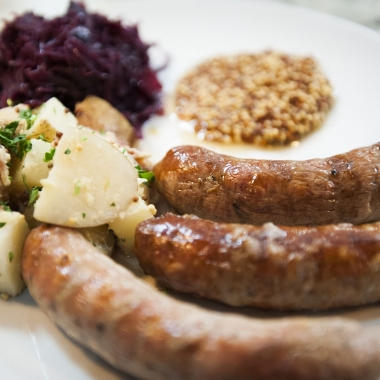 Three German sausages on a plate with German patato salad, rotessa sauerkraut and whole grain mustard. (Photo: Red's Table