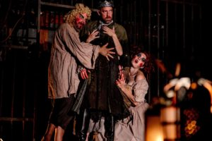 Witches gather around Macbeth, the new king of Scotland in a scene from the Folger Theatre's production. (Photo: Brittany Diliberto)