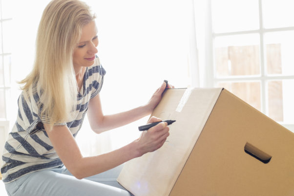 Woman labeling moving box at home. (Photo: Depositphotos)