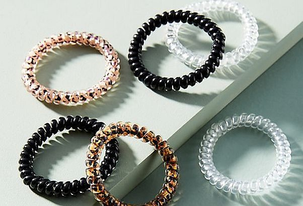 Six coiled head bands in white, black and brown laying on a white surface. (Photo: Anthropologie)