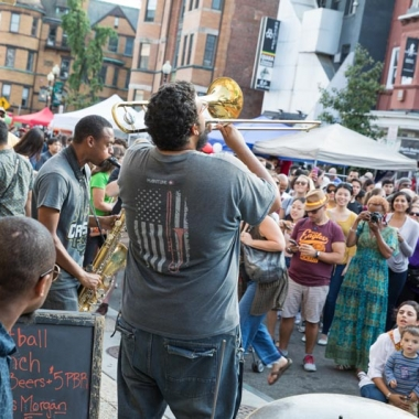 A crowd of people watching a band including a trumpet player at Adams Morgan Day. (Photo: Destination D.C.)