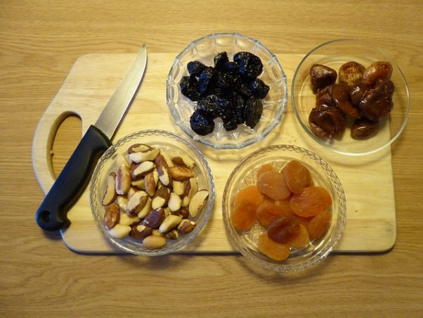 bowls of dried fruits and nuts on a cutting board with a knife laying beside it. (Photo: Regenwolke0/Pixaby)