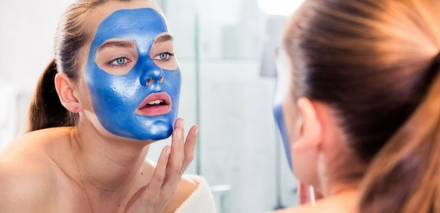A woman applying a blue facial mask in mirror. (Photo: Jake Rosenberg)