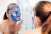 A woman applying a blue facial mask in mirror. (Photo: Jake Rosenberg)