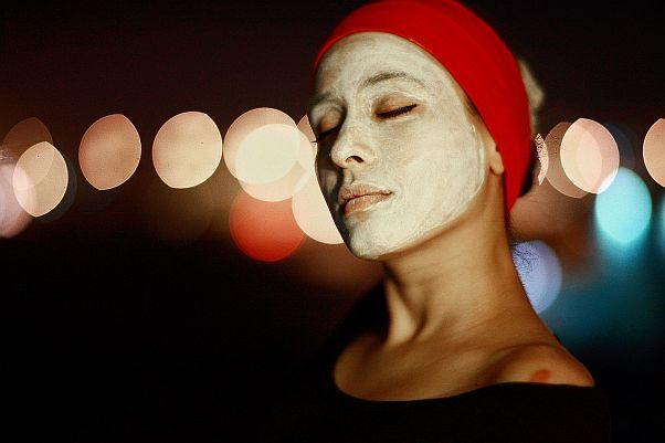 A woman with a green facial mask on her face with a red scarf holding her hair out of the way. (Photo: Pixabay)