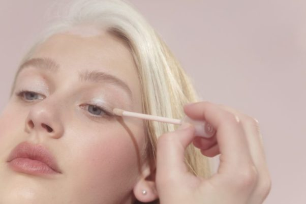 A woman applying light pink eyeshadow. (Photo: Glossier)
