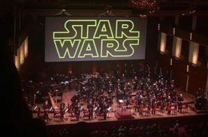 The National Symphony Orchestra performs the score to <em>Star Wars</em> while the movie plays on a screen hanging from the ceiling. (Photo: grandmariddle/Instagram)