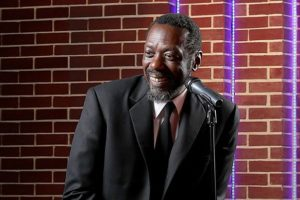 The actory playing Dick Gregory in Turn Me Loose on stage in front of a brick wall standing behind a microphone. (Photo: Tony Powell)
