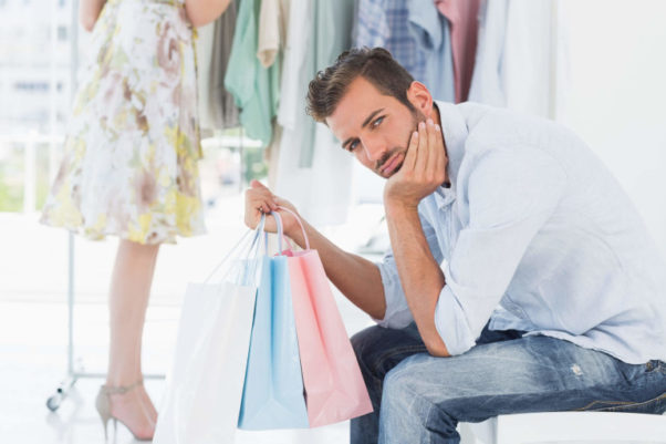 Man with shopping bag bored while woman searches clothes rack. (Photo: Shutterstock)