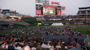People sitting on the playing field watching Opera in the Outfield on the giant scoreboard at Nationals Park. (Photo: Washington Nationals)