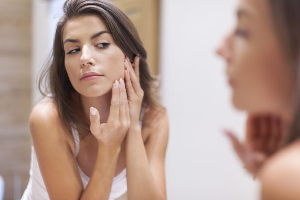 A woann looking at pimples on her cheek in a mirror. (Photo: Shutterstock)