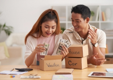 Young Asian couple putting money into boxes, saving for house, car and vacation. (Photo: Shutterstock)