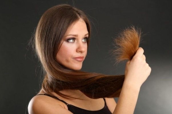 A woman holding split ends of her long hair, on black background. (Photo: Shutterstock)