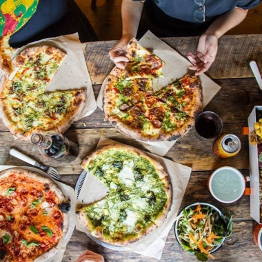 Diners sharing four different kinds of pizzas from Timber Pizza Co., which are on top of a wooden table. (Photo: Timber Pizza Co.)