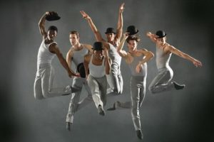 Male ballet dancers dressed in gray wearing black top hats jump into the air. (Photo: Dean Alexander)