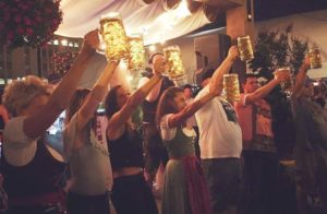 Men and women dressed in German garb hold filled steins in the air at Oktoberfest. (Photo: Wunder Garden/Facebook)