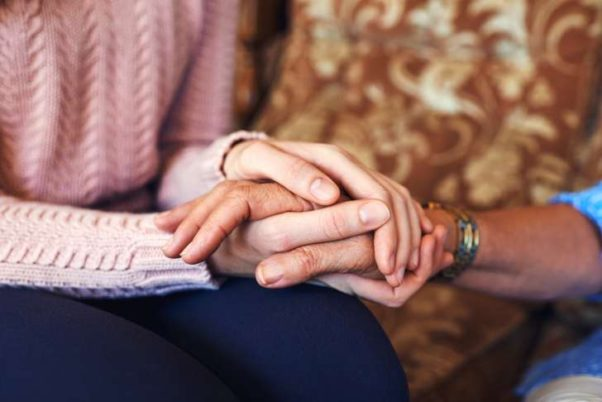 Cropped shot of unrecognizable women holding hands at home. (Photo: iStock)