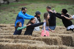 Adults and children walking through a hay bale maze with hands on the person in front's sholders. (Photo: Mount Vernon)