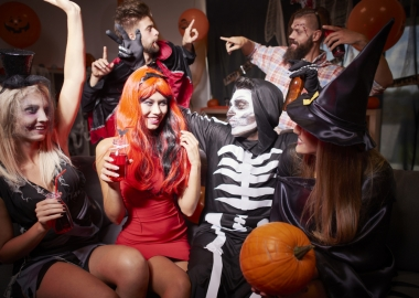 Three men and three women dressed in Halloween Costumes including witch, skelton and vampire at a house party. (Photo: Shutterstock)