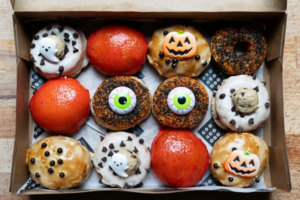 A dozen Halloween doughnuts decorated with pumpkins, ghosts and eyes in a box. (Photo: Scott Suchman)