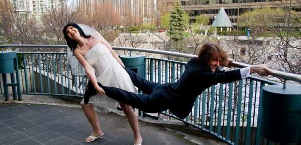 A bridge pulling a groom by his ankles while he hold onto a railing. (Photo: Alex Indigo/Flickr)