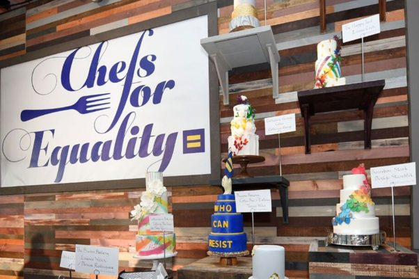 A wall with shelves holding tiered wedding cakes on them decorated in rainbow colors with a Chefs for Equality sign hanging on the wall. (Photo: Humar Rights Campaign)
