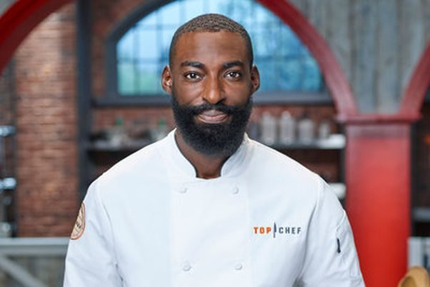 Headshot of Eric Adjepong in his Top Chef jacket on the set. (Photo: Bravo)